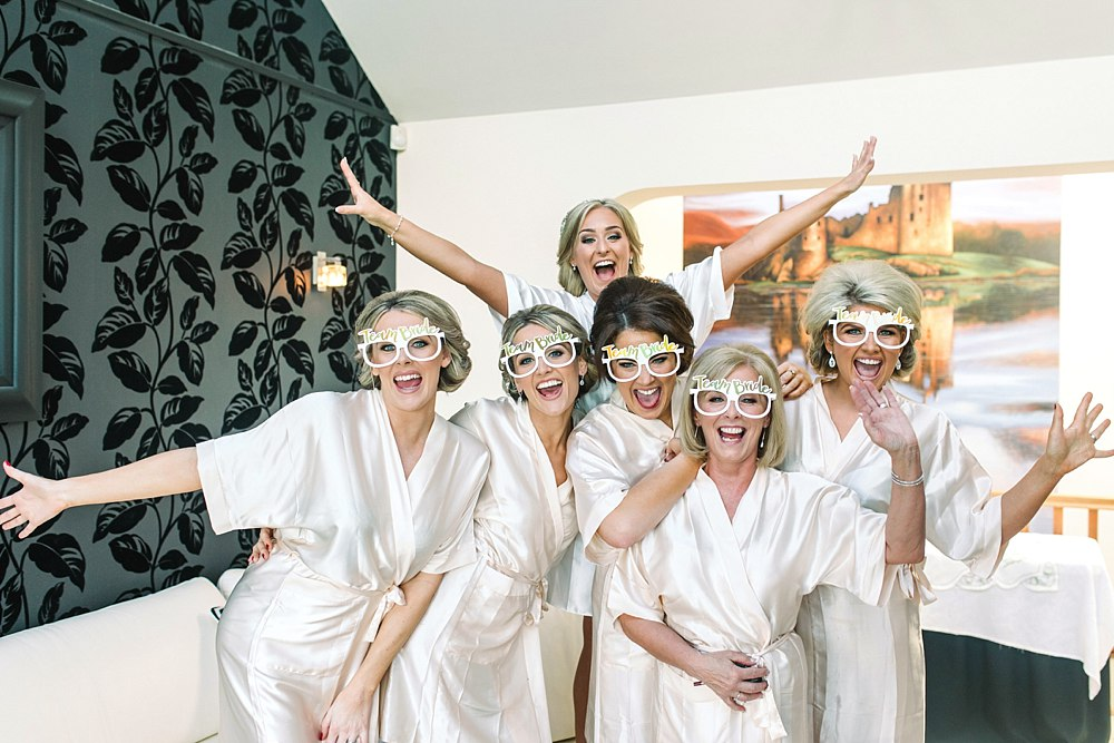 Bride, bridesmaids and mother of the bride on the wedding morning. Wearing wedding robes excited for the big day. Hair and makeup done for the wedding. Scotland Wedding Photographers
