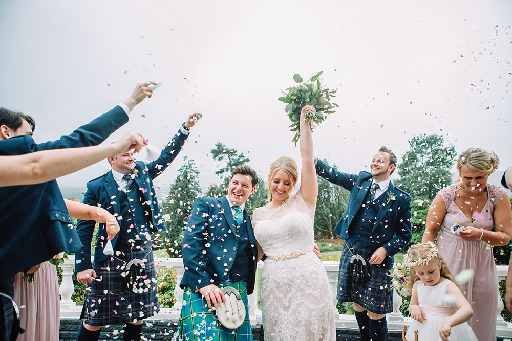 Bride and groom with bridal party for the confetti shot. Floral bouquet in the air. Lots of laughter and smiles. Happy Mr & Mrs.