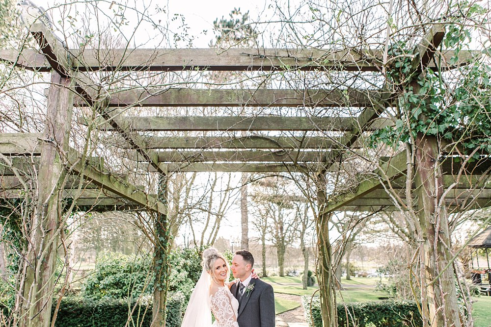 Beautiful blonde bride and Scottish kilted groom under ivy arch. Winter wedding. Light and bright with trees and greenery. Wild roots. Best ayrshire wedding photographers, colourful wedding,elegant wedding,light and airy wedding, light and bright wedding,romantic photographers ayrshire, Ayr wedding