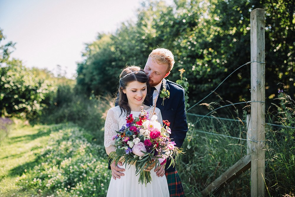 Brunette bride with redhead husband in a garden in love. Bride holding wildflowers, smiling being kissed by her bearded husband. Sunny day at the Secret Herb Garden in Edinburgh with lots of sunshine and greenery. Husband kissing bride on the side of her head on their wedding day.
