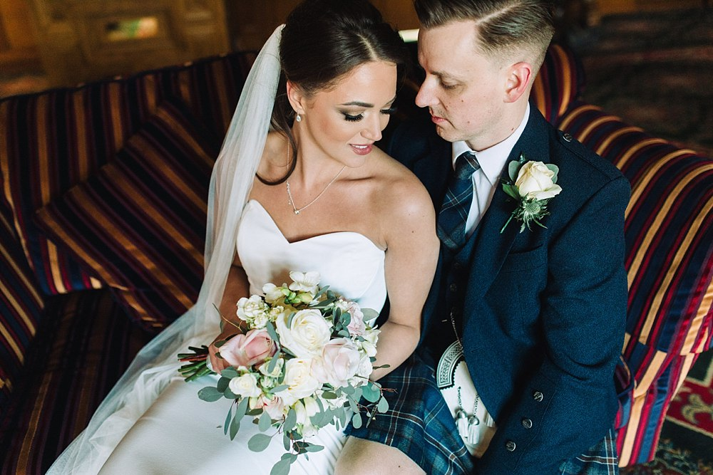 bride and groom sitting on the couch at Lochgreen House Hotel in winter time