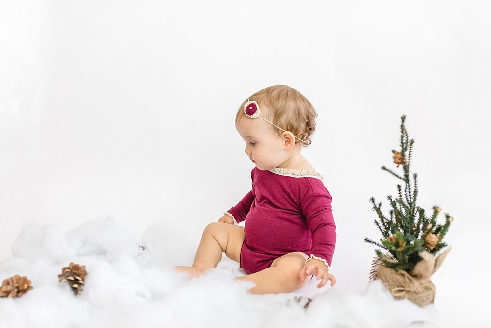 A little girl in a burgundy suit sitting on white fluff to resemble snow