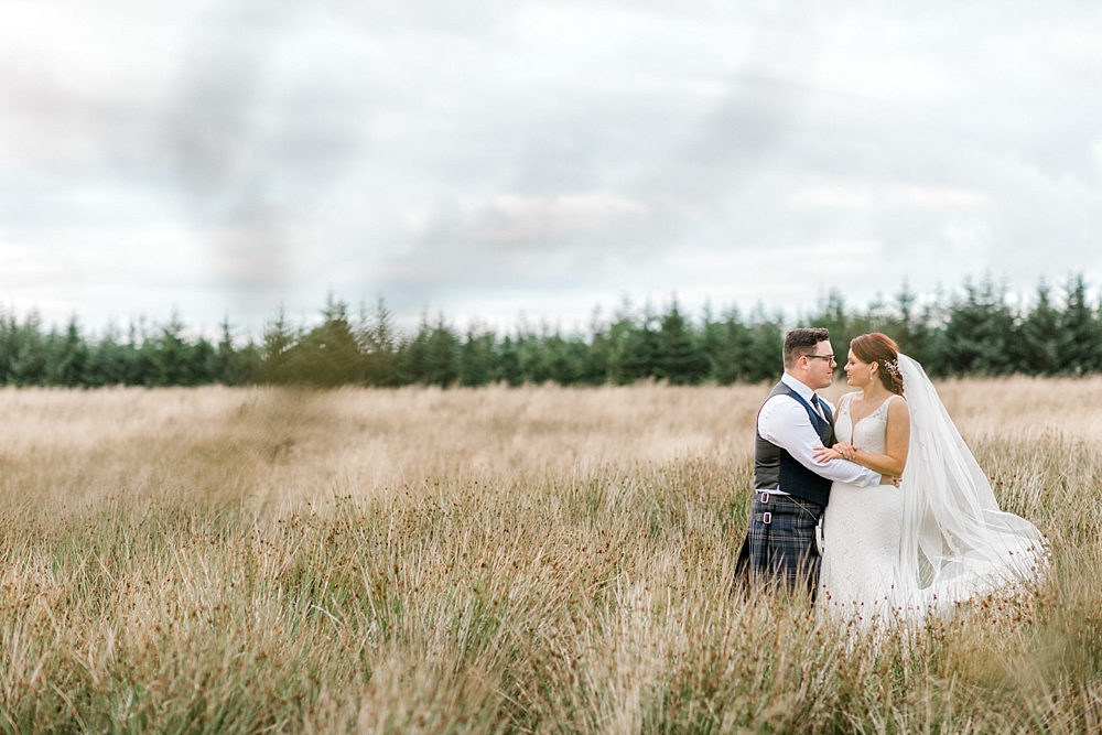 a bride and groom in a field with pine trees as a backdrop on the horizon.